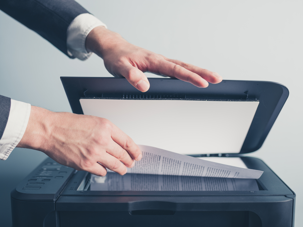 Gentleman scanning document on printer in a suit. Voted best in Miami and South Florida in document scanning, indexing, storage, imaging services with the highest imaging quality available